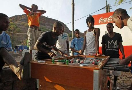 Children and young men played a game of foosball in the main plaza at Cidade Velhia.