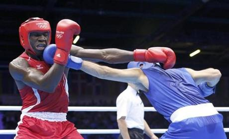 Namibia's Mujandae Kasuto fights against Hungary's Zoltan Harcsa, right, in their men's middle (75kg) round of 16 boxing match.