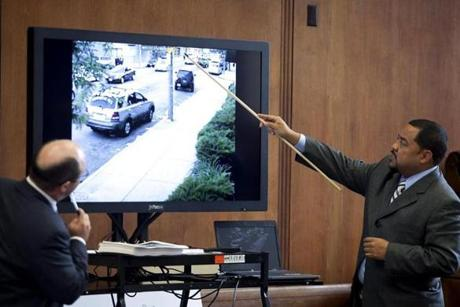 Officer Anthony Williams, who had witnessed the killing of Nicholas Fomby-Davis  points to a  screen showing images from a surveillance video during the trial in Suffolk Superior Court. Prosecutor Pat Haggan, left, tells jurors to focus on what happened that day May 30, 2010 and not why it happened.The reason, he says, will not make sense.