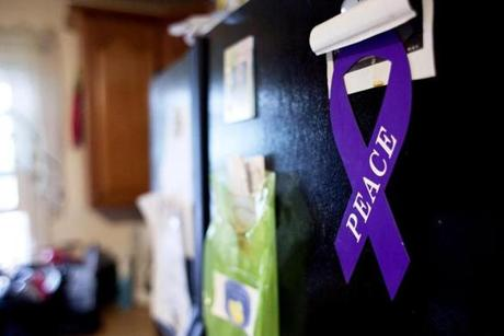 A peace magnet is displayed on the refrigerator of Theresa Johnson's home in Dorchester,