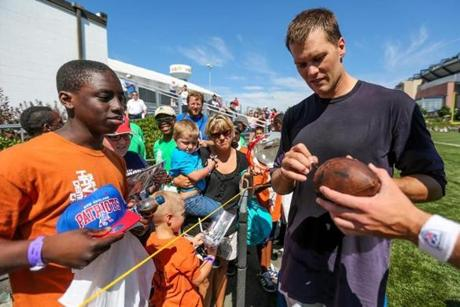 08/06/2012 FOXBOROUGH, MA Quarterback Tom Brady (cq) signs autographs for fans after a New England Patriots (cq) practice held at Gillette Stadium (cq) in Foxborough. (Aram Boghosian for The Boston Globe)