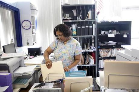 Latrina Fomby-Davis sorts through paperwork at the health center in Braintree where she works as the front desk supervisor. Since her son Nicholas's death, work has been a refuge.