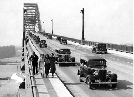 June 23, 1935: More than 30,000 automobiles traversed the great new Cape Cod Canal highway bridges on the opening of the new four-lane highways. A crowd of 100,000 witnessed the bridge dedication and parade. Hundreds of curious sightseers crossed the new structures on the wide five-foot sidewalk. This picture shows cars going across the Bourne Bridge as seen from the south.