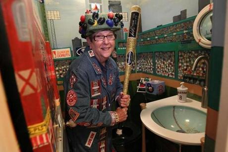 Red Sox fan Lynne Smith stood in her bathroom in Wellesley decorated with a Fenway mural, baseball sink and even includes Yankee toilet paper.