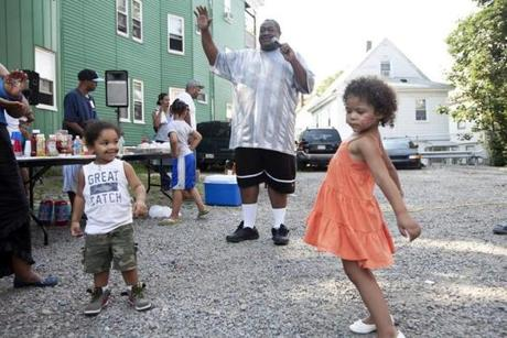 Nate Davis encourages his neighbors, including Isaiah Miranda, 2, and Jaylanny Fernandes, 3,  to have a dance contest at a cookout in a common area near his yard in early August.The block party is organized by his neighbor.