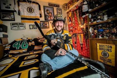 Boston Bruins fan Mike Penta, 39, sat in his bedroom surrounded by Bruins memorabilia at his home in Medford. The stick he is holding is signed by Zdeno Chara, his favorite player.