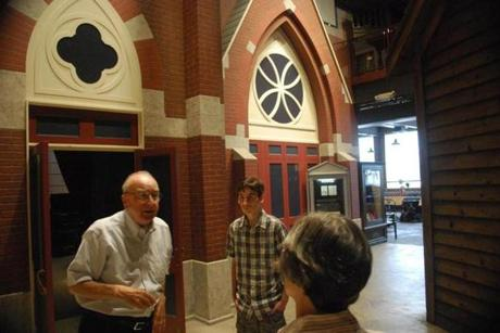 Co-director of the Museum of Work and Culture Ray Bacon leads a tour. In the background is the scaled facade of the Church of the Precious Blood, one of Woonsocket's French churches.