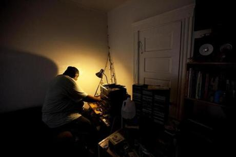 Nate Davis sits in the play room where his son, Nicholas, used to practice playing drums. He listens to favorite tunes from an LP called