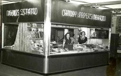 October 8, 1947: An ultra-modern subway newsstand — constructed with an eye toward more rapid, efficient service — opened on the mezzanine level of the Washington St. / Summer St. Station of the El. Larger display shelves, fluorescent lighting, and attractive neon advertising served to assist customers in purchases. The stand was made of stainless steel, decorated on the lower half with green structural glass.
