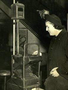 January 11, 1950: Peggy Matthews of Jamaica Plain inspected the new coin boxes. The new MTA fare increase from 10 cents to 15 cents meant a new open-throat fare box would now be used as substitute for the old dime fare boxes.