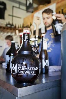 An employee fills growlers for visitors at Hill Farmstead Brewery in Greensboro, Vermont. photo by Monica Donovan for the Boston Globe