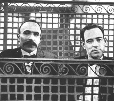 July 12, 1921: Bartolomeo Vanzetti and Nicola Sacco are shown in the prisoner's dock in Norfolk Superior Court where they were tried and convicted of first-degree murder of Frederick A. Parmenter and Alessandro Berardelli on April 15, 1920. During recesses, the two prisoners would be sequestered in a small room with this mesh and wire partition.