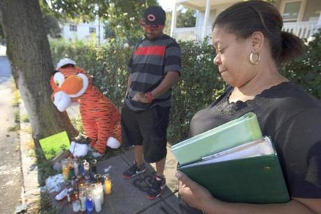 Mirna Luz Ramos visited a makeshift memorial for her son Jorge Fuentes as another son, Carmelo Fuentes, looked on.