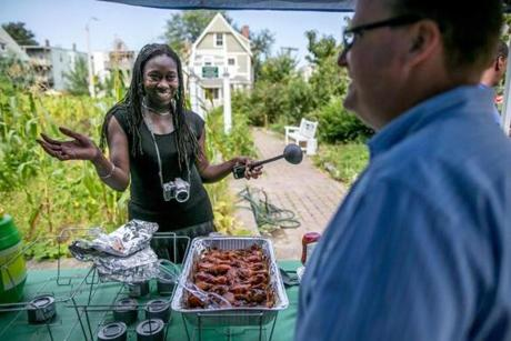 Jhana Senxian, left, founder of the Coleman Street Neighbors Association, served food in the community garden during a block party in September.