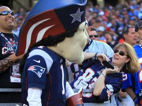 A fan tries for a photo of Patriots mascot Pat Patriot during the game.