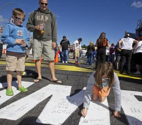 Loudon NH 9/23/12 Kathryn Miele (cq), 8, of Salem, NH signs her autograph on the finish line in front of her brother, William Miele (cq), 7, and father, Chris Miele before the start of the NASCAR Sprint Cup Slyvania 300 at the Loudon Motor Speedway on Sunday September 23, 2012. (Matthew J. Lee/Globe staff) slug: 24nascar Section: sports reporter: Michael Vega