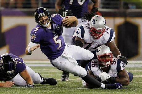 Quarterback Joe Flacco of the Ravens is brought down after scrambling for a first down by Kyle Love and Jermaine Cunningham.