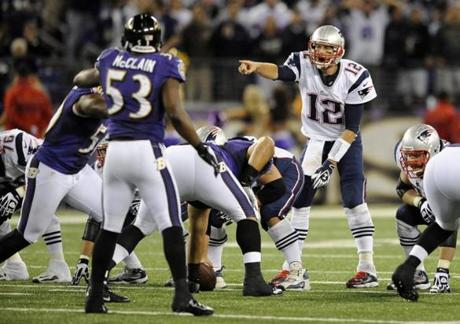 Tom Brady points across the line of scrimmage before running a play in the second half.