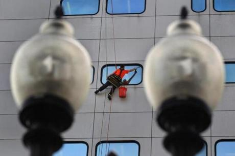 Boston-10/02/12- A window washer is suspended by rigging as he cleans windows on an office building on D Street in South Boston, framed through ornate street lights. Boston Globe staff photo by John Tlumacki (metro)