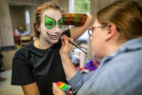 Kerry Leathers (left) had her clown makeup applied by Katia Greene, a makeup artist and performer, at Barrett's Haunted Mansion in Abington.
