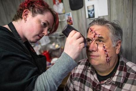 Makeup artist Katie Leishman (left) painted frightening features on the face of volunteer Rick Bizzozero of Hanover.