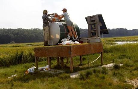 David Johnson and Kate Morkeski loaded a device that feeds fertilizer into the salt marsh on Plum Island.