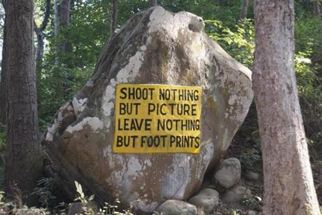A sign painted on a boulder within the Corbett National Park exhorts visitors to be responsible with a classic mantra.