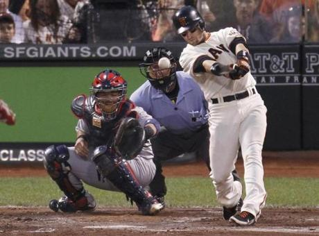 San Francisco Giants' Marco Scutaro hits a three RBI double as catcher Yadier Molina looks on during the fourth inning.