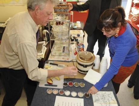 David J. Bowie of The Picklepot serves salt samples to Heather Cathcart during a Salem Food Tour.)