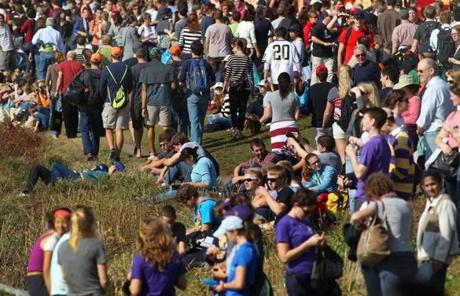 Spectators lined the banks of the Charles River along Memorial Drive in Cambridge.