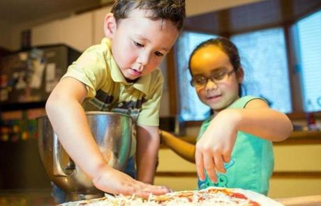 Fluto Shinzawa's children Wright, 3, and Hana, 6, help prepare dinner by spreading cheese over pizza dough.