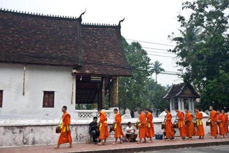 In the morning in Luang Prabang, monks walk in an alms procession past people waiting to put rice in the men's begging bowls, feeding the spirits of their ancestors.