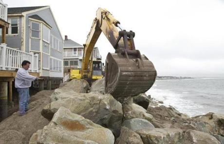 Workers on Sunday fortified the seawall at Oceanside Dr. in Scituate.