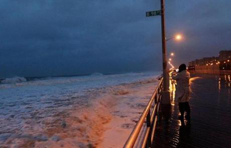 A woman took a photo of the ocean on the boardwalk at Rockaway beach in the Queens borough of New York early Monday.