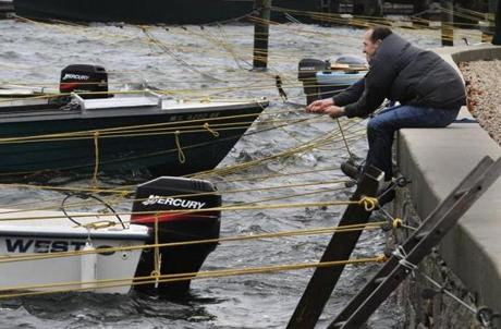 A man secured the lines on a boat in Eel Pond in Woods Hole during Hurricane Sandy