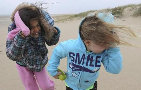 Jillian Webb (left) and Arianna Corso, of Dennis, in Chatham as Hurricane Sandy pelted them with wind and sand.
