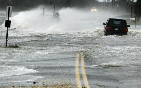 A car drove through water driven onto a roadway in Southampton, N.Y.