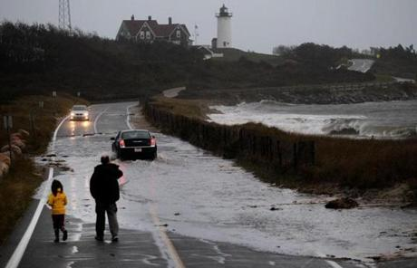 A car navigated a flooded Church Street in Woods Hole.