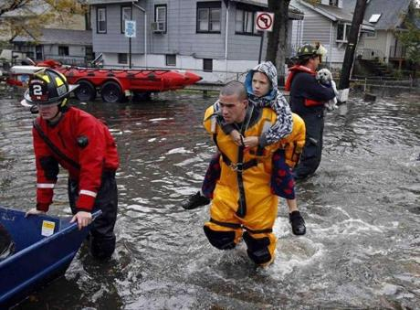 A rescue worker carries a boy on his back in Little Ferry, N.J.