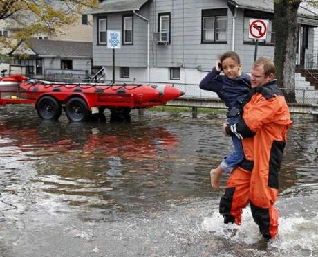A rescue worker carried a young girl to safety in Little Ferry, N.J.