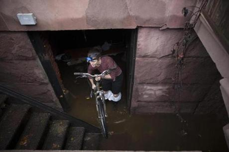 A woman removed a bicycle from a flooded basement on 14th street in New York.
