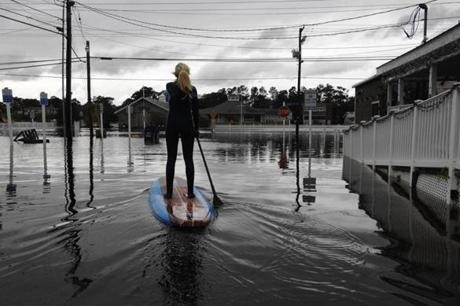 Zoe Jurusik, 20, paddle-boarded down a flooded street in Bethany Beach, Del.