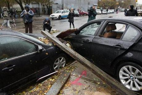 Onlookers took photographs of two cars that collided during flooding outside the Consolidated Edison power sub-station on 14th Street in New York.