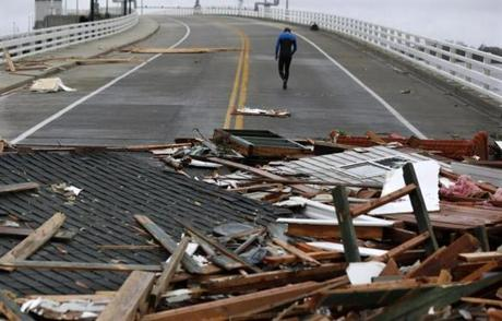 Currie Wagner walked away from the debris of his grandmother Betty Wagner's house on the Mantoloking Bridge in Mantoloking, N.J.