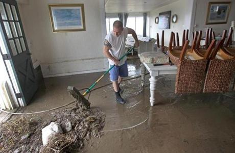 Jason Locke pushed mud out of his mother's home at Horseneck Beach in Westport after the storm.