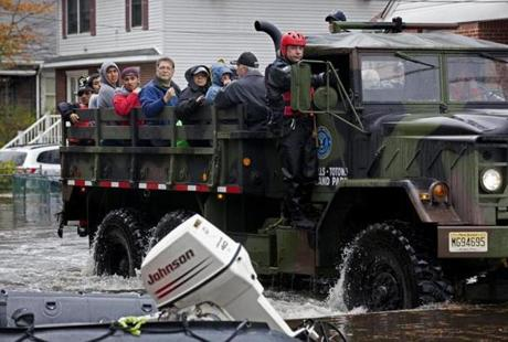 People rescued from floodwaters rode on a large truck in Little Ferry, N.J.