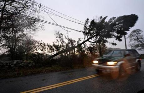 A car passed a tree lying on power lines, the morning after Hurricane Sandy in Dartmouth.