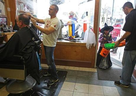 Bob Foster gave candy to trick-or-treater Sarina Krishnaswamy, 8, at the La Flamme Barber Shop in Lexington as barber John Makris gave John Reece a haircut.