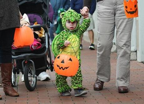 Lexington, MA., 10/31/12, The children of Lexington trick-or-treated at the downtown businesses. Fourteen-month-old Nia Simpson makes her way along Massachusetts Ave. She is dressed as a turtle. Section: Metro Suzanne Kreiter/Globe staff
