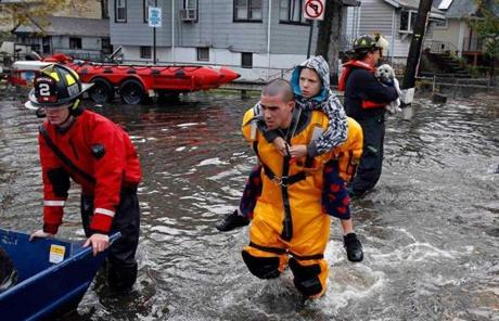 A rescue worker helped a young boy evacuate an area in Little Ferry, N.J., on Tuesday, that was hit by flood waters.